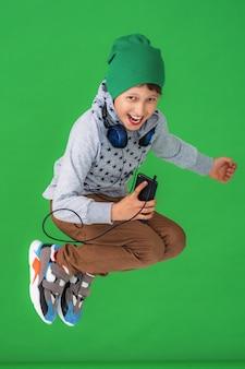 O menino pequeno nas calças de brim um hoodie e um chapéu salta isolado em um verde.