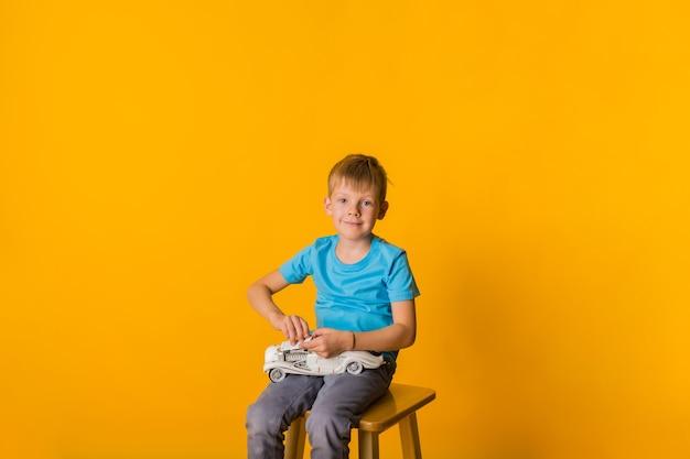O menino pequeno se senta em uma cadeira e brinca com uma máquina de escrever retrô branca e olha para a câmera em um fundo amarelo com espaço para texto