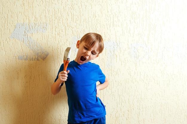 O menino pinta a parede com um pincel. a criança segura um pincel para pintar. ajudante. criança se divertindo durante a renovação de seu quarto.