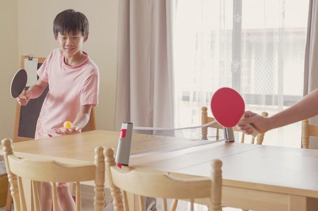 O menino pré-adolescente asiático misto saudável que joga o tênis de mesa na mesa de jantar em casa, exercício da interpolação, aptidão da criança, permanece saudável e apto durante o distanciamento social, conceito do isolamento