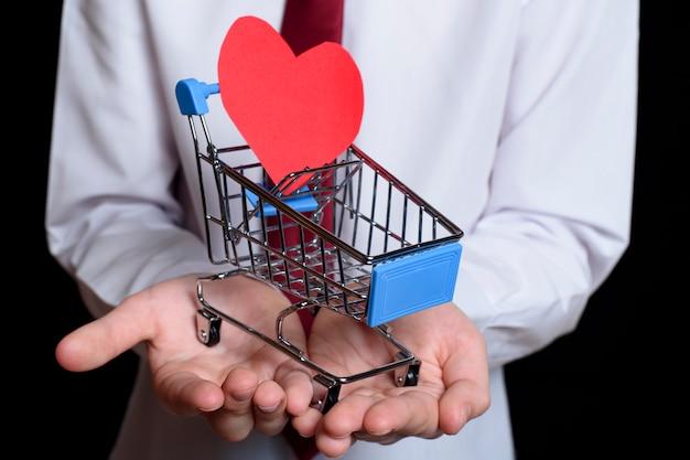 O menino prende um carrinho de compras de metal com um cartão postal em forma de coração dentro.