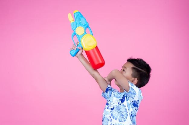 O menino prende uma arma de água em um fundo cor-de-rosa.