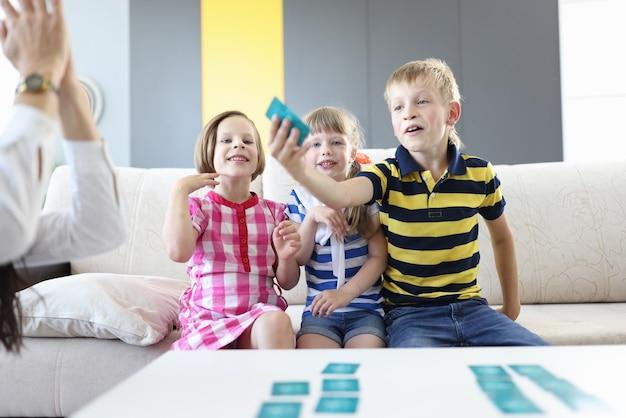 O menino puxou o cartão do vencedor e duas meninas se alegraram uma ao lado da outra olhando e sorrindo