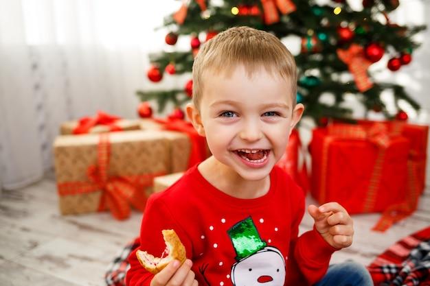 O menino que se senta perto da árvore de natal para o ano novo. decoração de natal com presentes, uma criança perto da árvore de natal come croissants e sorri