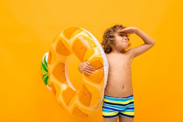 O menino ruivo europeu de cabelos cacheados com um círculo de natação está procurando alguém