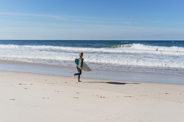 O menino se amassa na praia antes de navegar e corre na água com uma prancha de surf