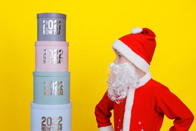 O menino se levanta e olha para a torre de caixas redondas de presente com a inscrição ano novo 2022