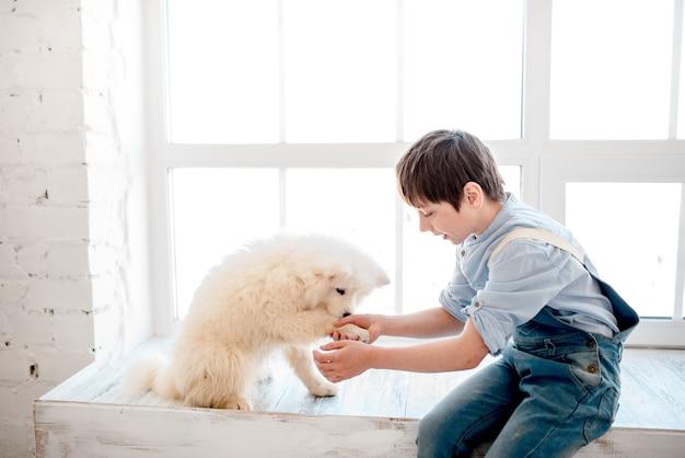 O menino se senta no parapeito da janela e segura a pata de um cachorrinho branco e fofo