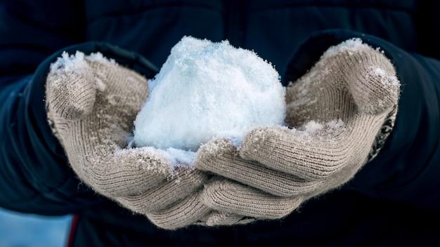O menino segura uma bola de neve nas mãos