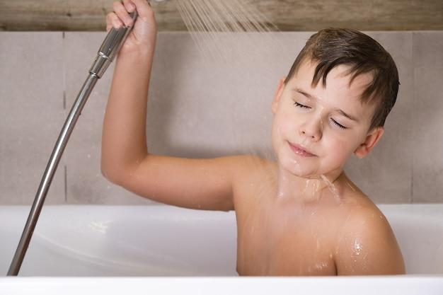 O menino segurando o chuveiro e lavando a cabeça no banheiro. infância saudável e feliz