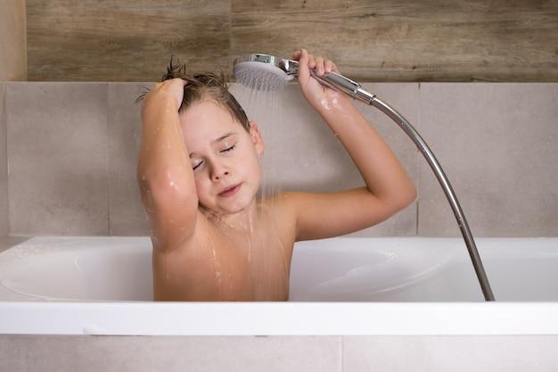 O menino segurando o chuveiro e lavando a cabeça no banheiro saudável na infância Foto Premium