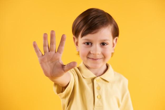 O menino smilling pequeno mostra a palma da mão.