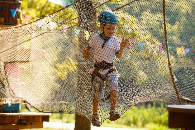 O menino sobe em um parque de cordas