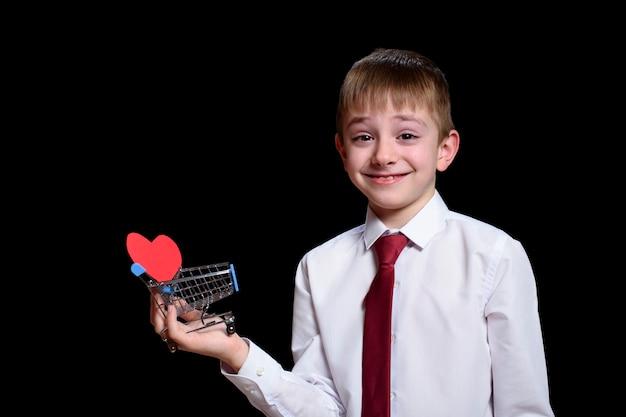 O menino sorridente de camisa clara e gravata segura um carrinho de compras de metal com um cartão postal em forma de coração dentro.