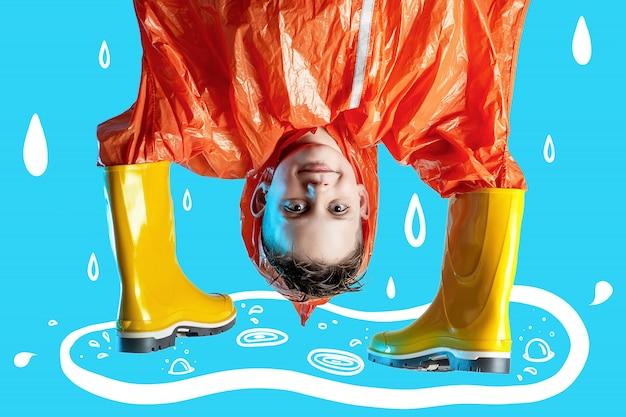 O menino sorridente na capa de chuva laranja enfiou as mãos em botas de borracha sobre fundo azul