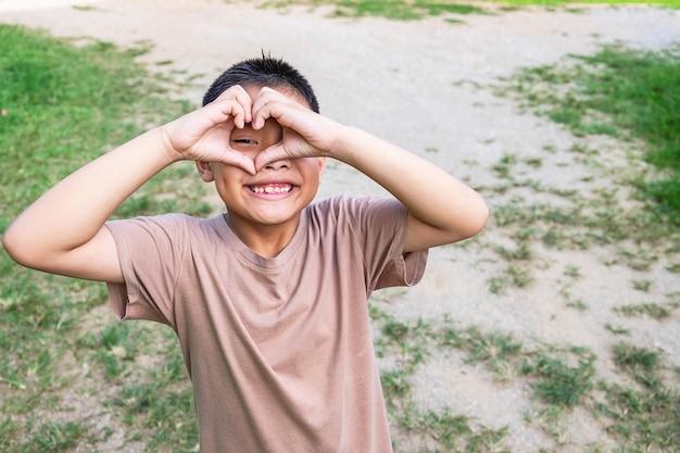 O menino sorriu feliz feliz, forma de coração com as mãos