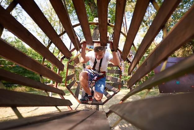 O menino supera o obstáculo no parque de cordas.