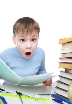 O menino surpreendeu atrás de uma mesa com livros