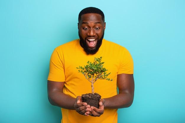 O menino surpreendido feliz mantém uma pequena árvore pronta para ser plantada. conceito de arborização