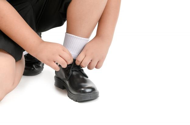 O menino tailandês do estudante está amarrando o sapato do estudante dos laços isolado