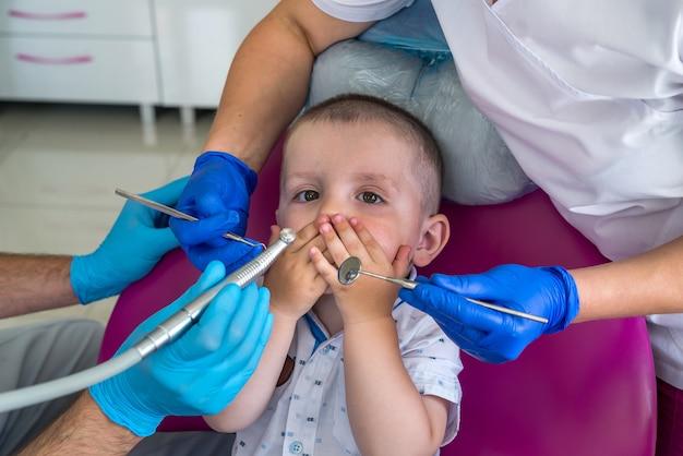 O menino tem medo de procedimentos odontológicos e fecha a boca com as mãos