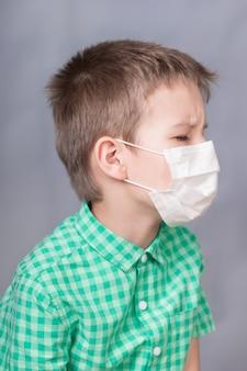 O menino tosse com uma máscara médica