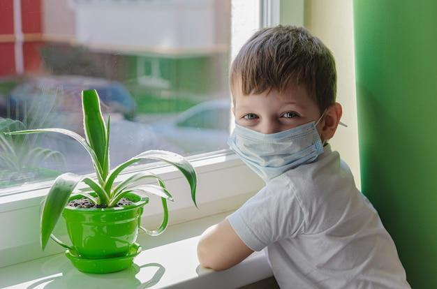 O menino triste com uma máscara médica (protetora) quer andar na rua, uma criança senta-se no peitoril da janela e anseia. quarentena (auto-isolamento) devido a infecção por coronovírus