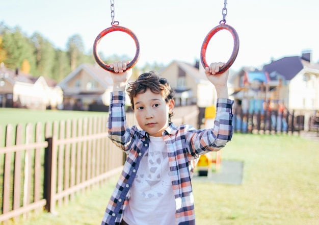 O menino tween quieto pensativo prende nos anéis no campo de jogos, vila da cabana no fundo
