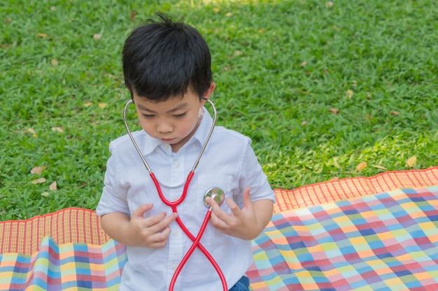 O menino usa estetoscópios e sente-se feliz no parque do jardim.