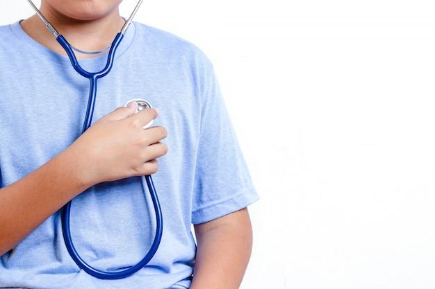 O menino usa um estetoscópio médico para ouvir o som do seu próprio coração.