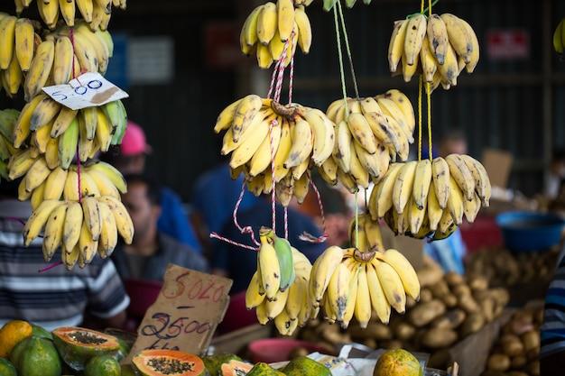 O mercado de bananas e as pessoas estão comprando frutas no mercado dos agricultores nas maurícias