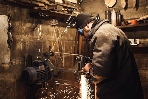 O mestre afia a faca em um amolador de correia e muitas faíscas são produzidas.