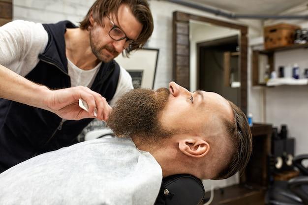 O mestre barbeiro faz penteados e estilos. barbearia do conceito. estilo e corte de barba. estilo de barba preta.