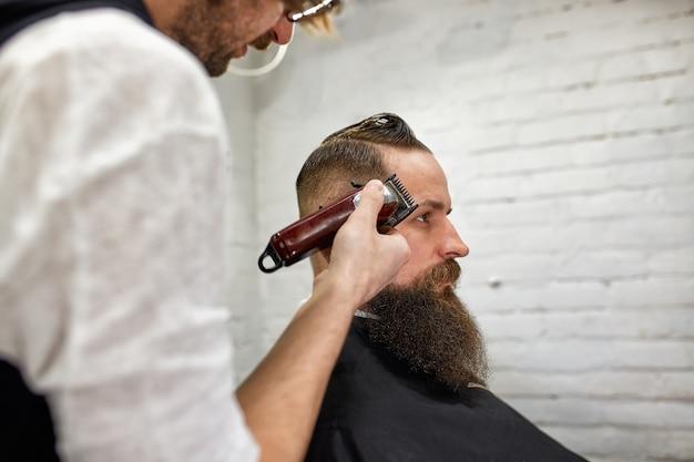 O mestre barbeiro faz penteados e estilos. barbearia do conceito. estilo e corte de barba.
