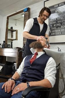 O mestre barbeiro faz penteados e estilos. barbearia do conceito.