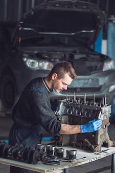 O mestre coleta um motor reconstruído para o carro.