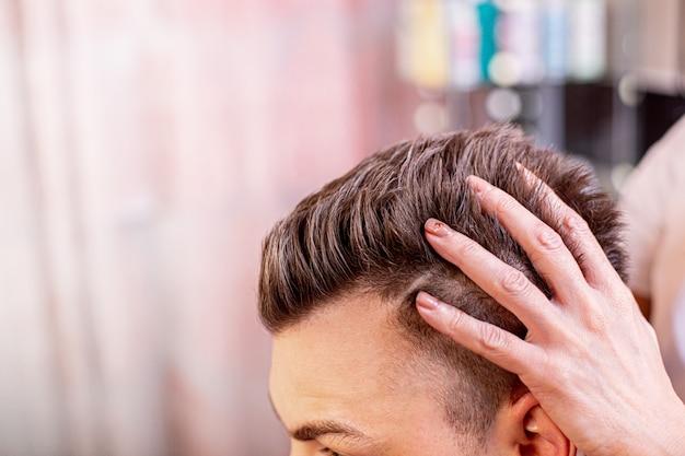 O mestre coloca os cabelos de um homem em uma barbearia, um cabeleireiro faz um penteado para um jovem com a ajuda de gel e verniz.