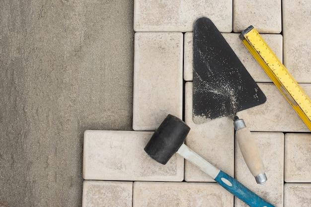 O mestre coloca pedras de pavimentação em camadas