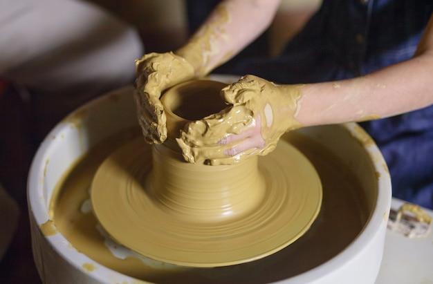 O mestre com a criança molda um jarro de barro.