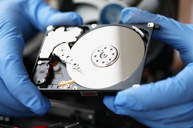 O mestre com luvas mostra close up do disco rígido do computador