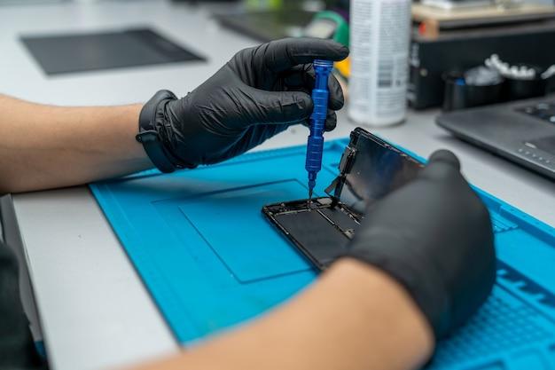 O mestre conserta o smartphone e o desmonta com uma chave de fenda