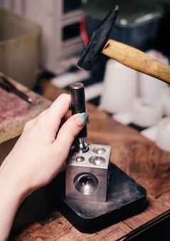 O mestre cria um detalhe das jóias artesanais na oficina. derrubando o hemisfério.