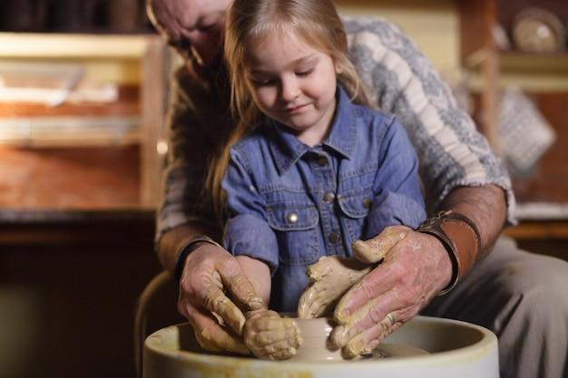 O mestre da criança molda um jarro de barro.