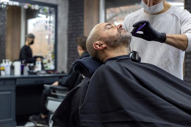 O mestre da máscara facial está cortando a barba de um cliente no salão. cuidados com a barba em época de pandemia