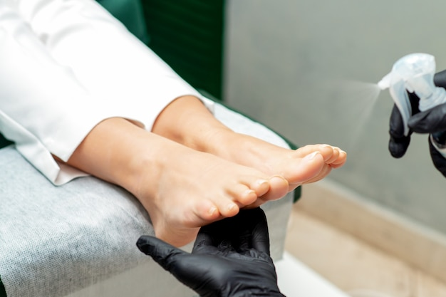 O mestre da pedicure pulveriza os pés femininos enquanto faz a pedicure em um salão de beleza, close-up.