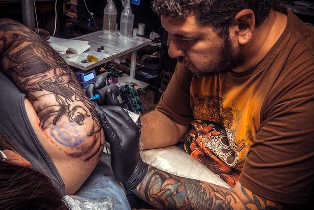 O mestre da tatuagem cria uma tatuagem no estúdio.
