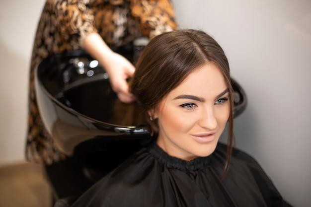 O mestre de corte de cabelo lava o cabelo de seu cliente