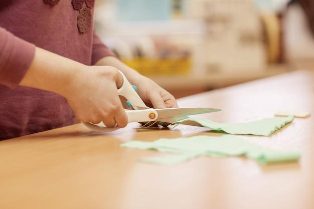 O mestre de costura corta um pedaço de pano com uma tesoura para trabalhar com o produto