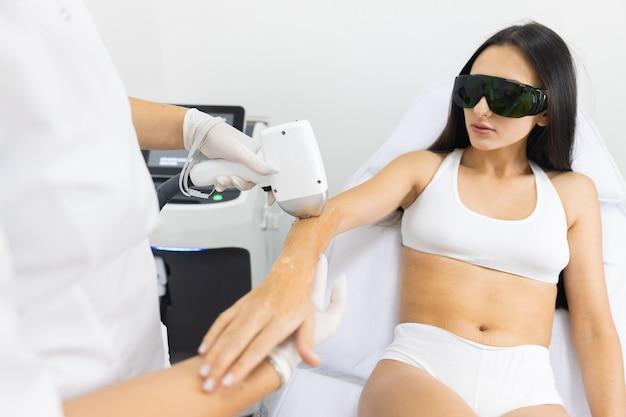 O mestre de depilação a laser remove pelos das mãos de pacientes femininas