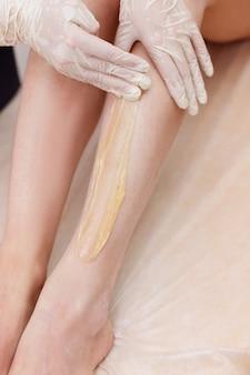 O mestre de depilação aplica as pernas de pasta de açúcar